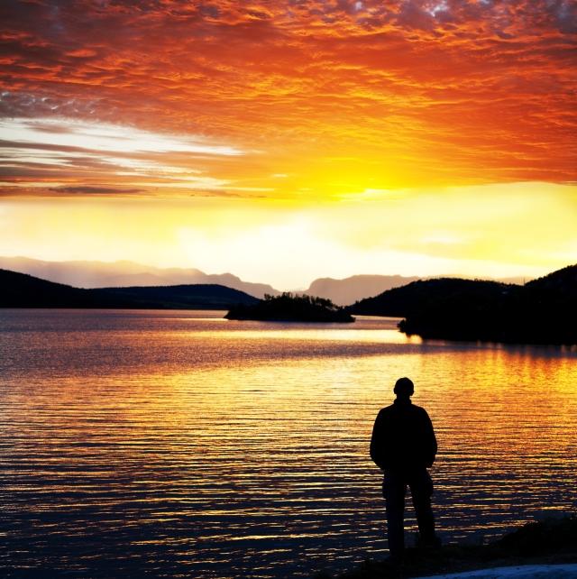 man silhouette at sunset lake, Norway